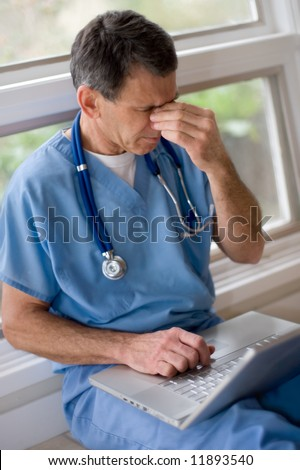 Mature doctor in blue scrubs sitting on floor with laptop, rubbing his tired eyes, looking overworked and tired