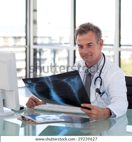 Mature Doctor looking at an x-ray in a hospital