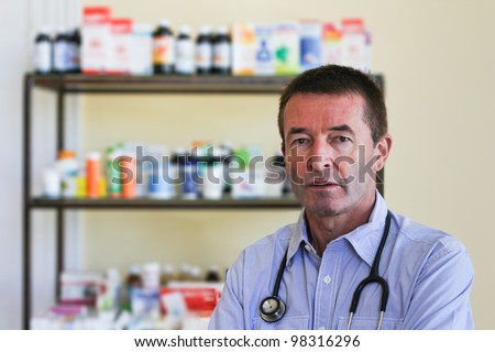 Mature Doctor Standing In Front Of A Shelf Full Of Medicine