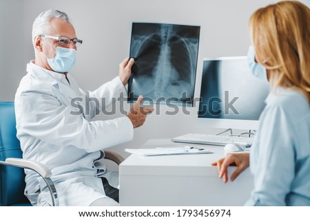 Mature doctor wear protection face mask showing female patient x-ray shot in clinic office. Coronavirus chest X-ray. Foto stock ©