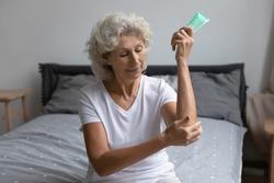 Mature elderly 60s woman applying cream on elbow in bedroom. Senior lady moisturizing dry body skin, taking treatment against eczema, injury or arthritis. Cosmetics, dermatology, skincare concept