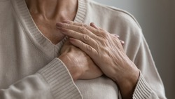 Mature elderly woman feeling heart pain, touching chest with both hands. Thankful senior lady expressing gratitude, love, trust, thanking god, making grateful honor kindness gesture. Close up