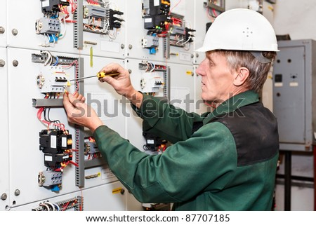 Mature Electrician Maintaining High Voltage Control Panel In Hard Hat With  Screwdriver #87707185