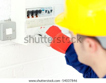 Mature electrician repairing a power plan at work