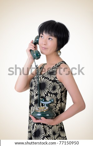 Mature elegant Asian woman holding old cellphone, closeup portrait on studio background.