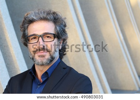 Mature elegant professional with glasses standing outside the office with copy space