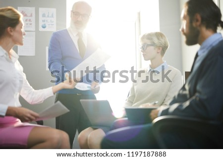 Mature employer giving his subordinates papers to look through while getting ready for conference