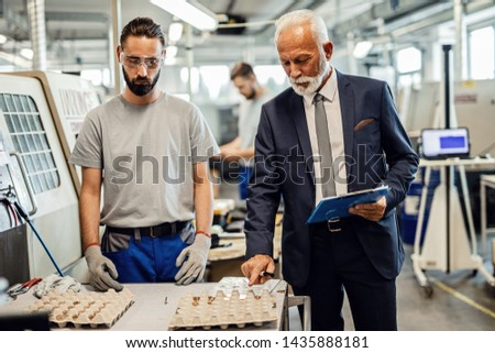 Mature engineer and manual worker analyzing finished merchandise in at factory plant.