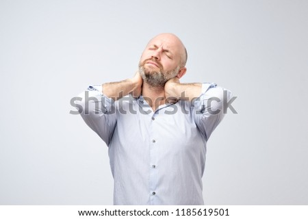 Mature european man with beard with neck pain. Hernia injury concept #1185619501