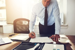Mature executive wearing a shirt and tie leaning over his desk in an office signing paperwork