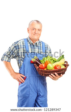 Mature farmer holding a basket full of fresh vegetables isolated against white background