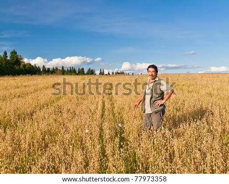 Mature farmer looking with satisfaction at his cultivated field and having care of wheat