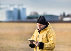 Mature farmer with tablet standing in field in winter time, with grain silos in background
