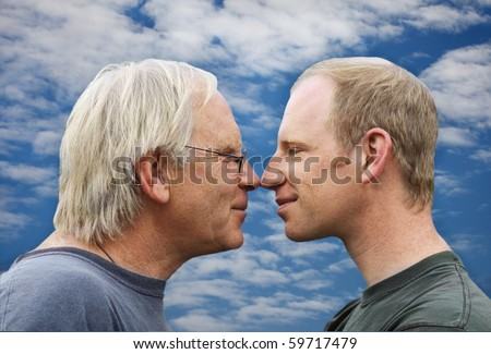stock photo : Mature father and adult son ,face to face in profile on sky