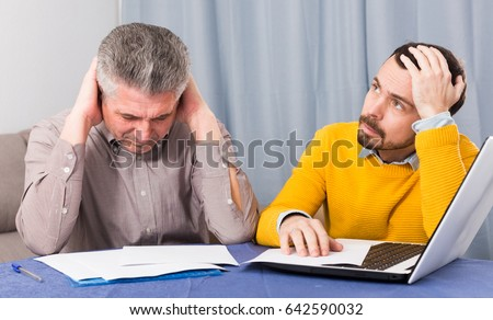 Mature father and young son are discussing an important contract at table #642590032