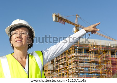 Mature female architect or construction engineer on building site supervising, wearing hardhat, with blurred background of construction site with crane.
