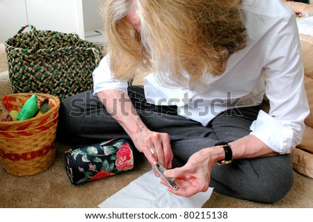 Mature female beauty doing her nails at home to relax after working all day.