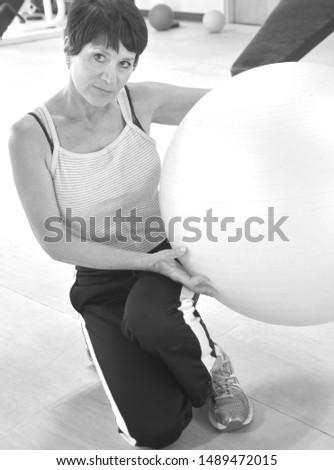 Mature female beauty with her yoga ball inside a health club.