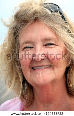 Mature female blond beauty posing outside.