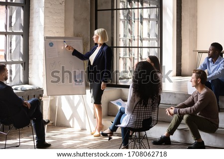 Mature female boss or coach talk present financial business project on whiteboard, confident middle-aged businesswoman make flip chart presentation for multicultural employees in office