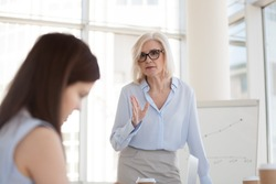 Mature female boss scolding young intern for bad work results at briefing, angry middle-aged businesswoman lecture, blaming employee, subordinate for business failure at company meeting, close up