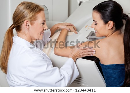Mature female doctor assisting young patient during mammography