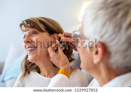 Mature female doctor hearing specialist in her office trying hearing aid equipment to a patient elderly senior woman. Senior woman adjusting hearing aid in doctor's office