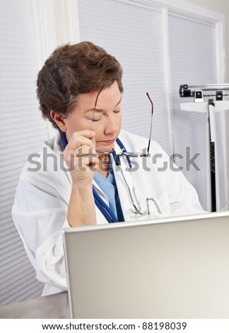 Mature female doctor or nurse in blue scrubs and lab coat, working on laptop, holding glasses, looking serious, stressed and competent.