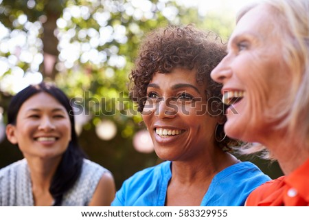 Mature Female Friends Socializing In Backyard Together