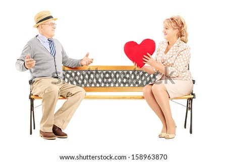 Mature female giving a red heart to a surprised man, seated on a bench, isolated on white background