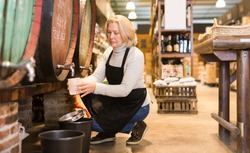Mature female seller pouring draft wine from wooden barrels to small plastic can in local shop