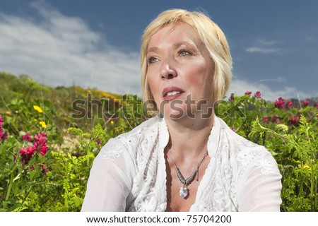 stock photo mature female senior model with blue sky and flowers and foliage in background 75704200 Chubby tits bbw Karla Lane