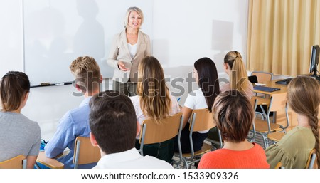 Mature female speaker giving presentation for students in lecture hall  #1533909326