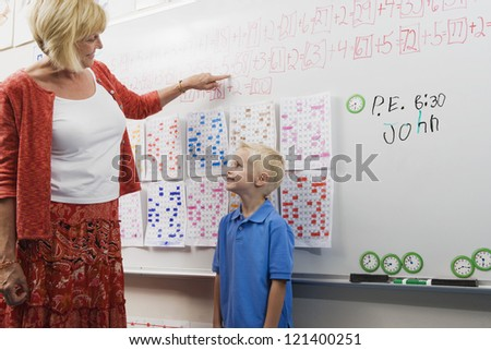 Mature female teacher teaching maths to a preadolescent boy on whiteboard