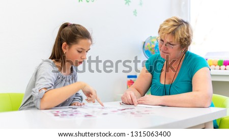 Mature female therapist working with a teenage girl with learning difficulties to master logical tests.
