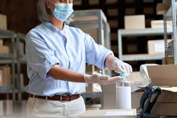 Mature female warehouse worker, post office employee, entrepreneur, small business owner wears face mask using sanitizer cleaning hands working in shipping delivery stock. Covid 19 protection, closeup