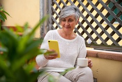Mature friendly woman looking the smartphone - She is sitting on the terrace her home during the lockdown and buying objects online for not exit from house - Concept of technology, safe and protection