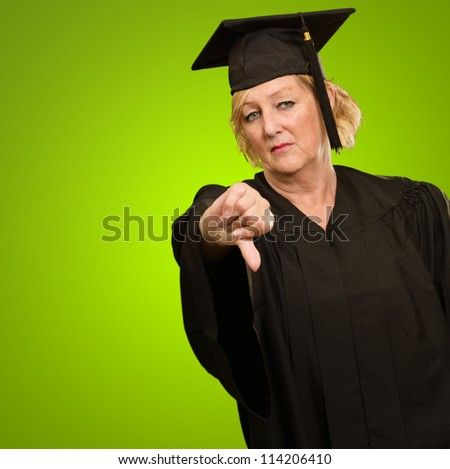 Mature Graduate Woman Showing Thumb Down Isolated On Green Background
