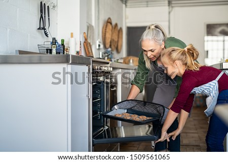 Mature grandmother wearing oven mitts and removing chocolate cookies from oven. Senior grandma taking hot bakeed biscuits out of the oven. Old woman and granddaughter cooking together at home.