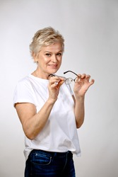 Mature grey haired slim  woman wearing white top and jeans holding rounded glasses