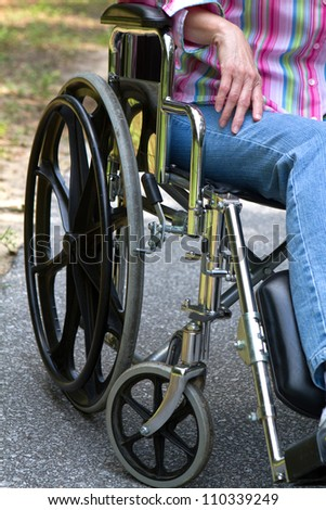 Mature handicapped disabled woman sits waiting in a wheelchair.