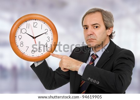 mature handsome business man holding a clock
