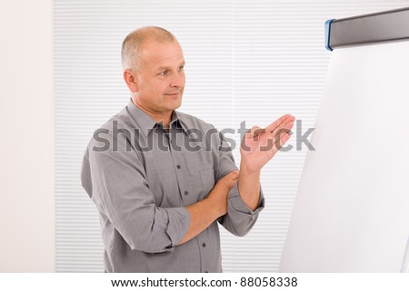 Mature handsome businessman pointing at empty flip chart looking aside