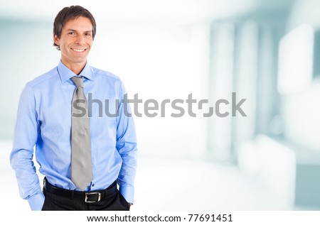 Mature handsome businessman smiling in an office environment