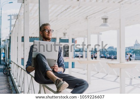 Mature handsome man relaxing outside and working on his laptop.