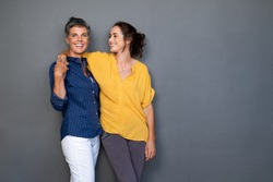 Mature happy women embracing each other against grey wall with copy space. Happy laughing ladies standing on gray background. Cheerful middle aged woman with hand on shoulder of her stylish friend.