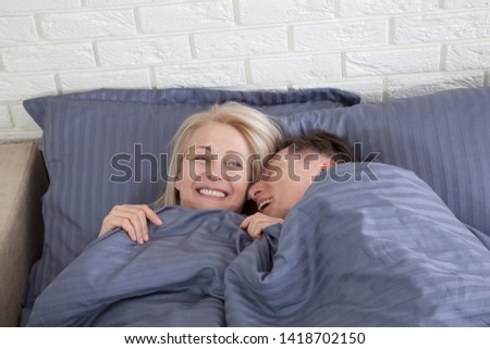 Mature heterosexual beautiful couple lying on bed in bedroom at home #1418702150