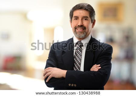 Mature Hispanic Businessman with arms crossed isolated on a white background