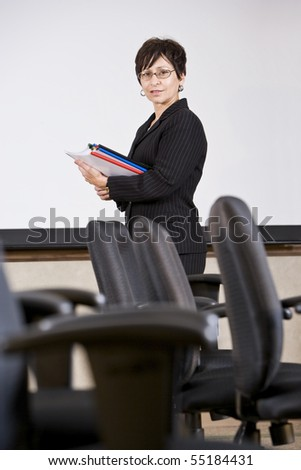 Mature Hispanic professional woman standing with empty chairs - businesswoman or university teacher