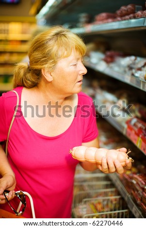 stock photo : Mature Housewife buying sausage in supermarket